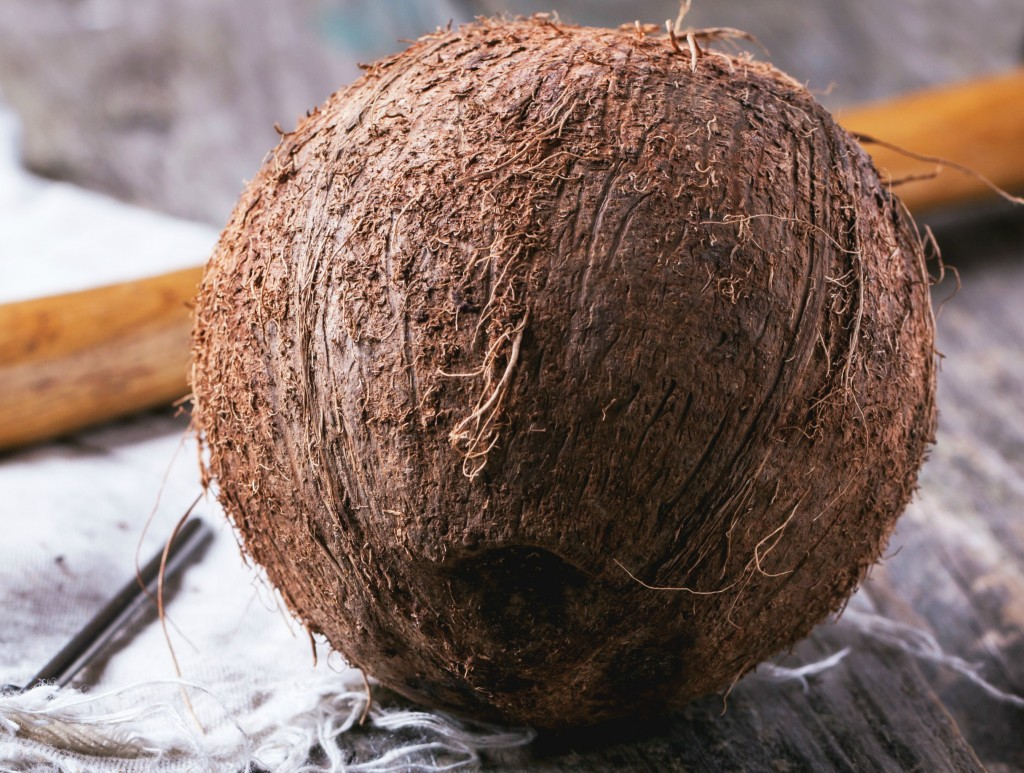Whole coconut with wooden handle in background
