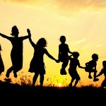 silouettes of 7 children jumping against a sunset or sunrise background