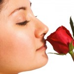 A girl smelling a red rose