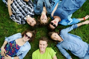 6 people lying on their backs in the grass with their heads pointing in to the center of a circle