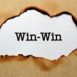 the words Win-Win appearing through a burned out hole in brown paper.