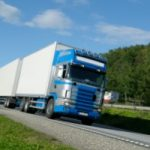 blue cab delivery truck driving on highway facing you. Photo credit GraphicStock